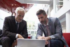 使用膝上型计算机的两个商人在现代办公室大厅地区  免版税库存图片
