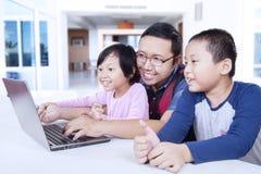 使用膝上型计算机的两个孩子有爸爸的在家 免版税库存照片