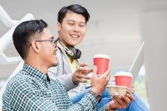 使用膝上型计算机的两个年轻亚裔人,当放松在断裂期间时 免版税库存照片