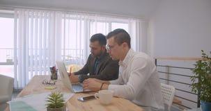 使用膝上型计算机的两个成人成功的商人画象和有讨论在办公室户内 股票录像