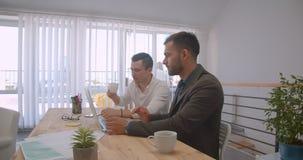 使用膝上型计算机的两个成人白种人商人画象和有交谈在办公室户内 影视素材