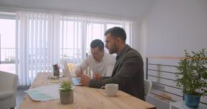 使用膝上型计算机的两个成人白种人商人画象和有交谈在办公室户内 股票视频
