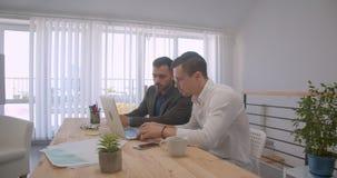 使用膝上型计算机的两个成人白种人商人画象和有讨论在办公室户内 影视素材