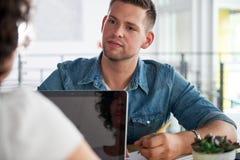 使用膝上型计算机的两个成功的商人的图象在交谈时 库存图片