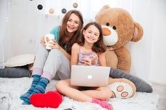 使用膝上型计算机的两个逗人喜爱的愉快的姐妹在儿童居室 免版税图库摄影