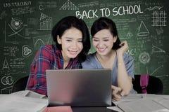 使用膝上型计算机的两位大学生在教室 库存照片