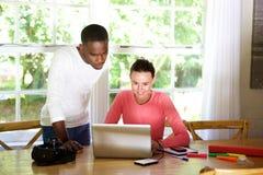 使用膝上型计算机的两位年轻照片艺术家 免版税库存图片