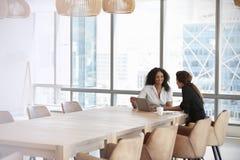 使用膝上型计算机的两名女实业家在会议室会议 免版税图库摄影