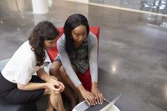 使用膝上型计算机的两名女实业家在现代办公室大厅  免版税库存照片