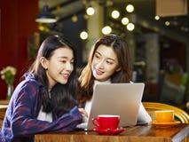 使用膝上型计算机的两名年轻亚裔妇女在咖啡店 库存图片