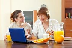 使用膝上型计算机的两名愉快的妇女在早餐期间 免版税库存照片