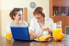 使用膝上型计算机的两名愉快的妇女在早餐期间 库存图片