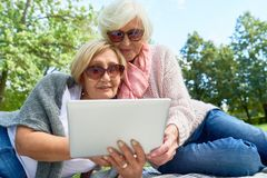 使用膝上型计算机的两名资深妇女在公园 免版税库存照片