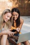使用膝上型计算机的两微笑的少女在公园 库存图片