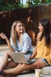 使用膝上型计算机的两微笑的少女在公园 图库摄影