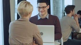 使用膝上型计算机的两年轻买卖人在现代办公室大厅  股票视频