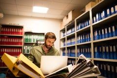 使用膝上型计算机的严肃的商人在文件存储室 库存照片