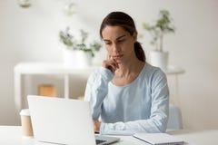 使用膝上型计算机的严肃的女生,运转在困难的projec 免版税库存照片