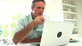 使用膝上型计算机的中世纪人和吃早餐 股票视频