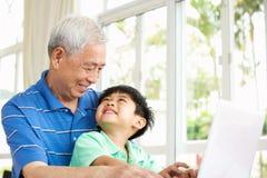 使用膝上型计算机的中国祖父和孙子 免版税库存图片