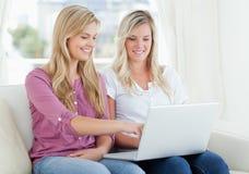 使用膝上型计算机的二名微笑的妇女 库存图片