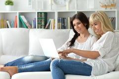 使用膝上型计算机的二名美丽的妇女 库存图片