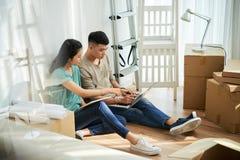 使用膝上型计算机的亚洲夫妇在拆迁时 图库摄影