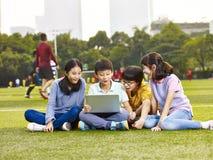 使用膝上型计算机的亚裔基本的学童户外 库存图片
