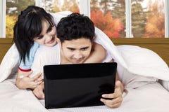 使用膝上型计算机的亚洲夫妇在床上 免版税库存照片