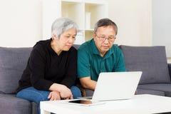 使用膝上型计算机的亚洲老夫妇 免版税库存照片