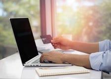使用膝上型计算机的人为购物在网上在办公室 免版税库存图片