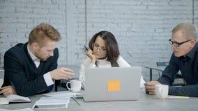 使用膝上型计算机的人们和做讨论在办公室 股票录像