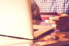 使用膝上型计算机的人和拿着与网上购物或互联网银行业务概念的信用卡 库存图片