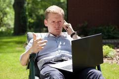 使用膝上型计算机的人和谈话在电话 免版税库存图片