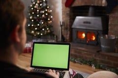 使用膝上型计算机的人在装饰的屋子里为圣诞节 图库摄影
