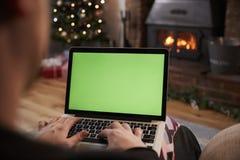 使用膝上型计算机的人在装饰的屋子里为圣诞节 免版税图库摄影