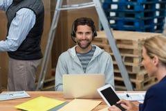 使用膝上型计算机的人在仓库 免版税图库摄影