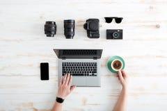 使用膝上型计算机的人的手和喝在桌上的咖啡 库存照片
