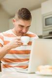 使用膝上型计算机的人饮用的咖啡 免版税库存图片