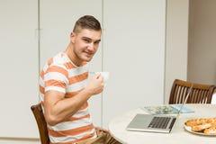 使用膝上型计算机的人饮用的咖啡 库存图片