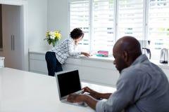 使用膝上型计算机的人,当妇女阅读书在背景时 免版税库存图片