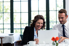使用膝上型计算机的企业同事,当开会议时 免版税库存图片