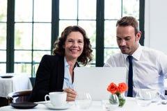 使用膝上型计算机的企业同事,当开会议时 库存照片