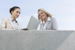 使用膝上型计算机的低角度观点的女实业家,当站立与大阳台的同事反对天空时 免版税库存照片