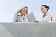 使用膝上型计算机的低角度观点的女实业家,当站立与大阳台的同事反对天空时 库存图片