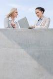使用膝上型计算机的低角度观点的女实业家,当站立与大阳台的工友反对天空时 库存照片