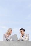 使用膝上型计算机的低角度观点的被集中的女实业家,当站立与大阳台的工友反对天空时 免版税图库摄影