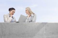使用膝上型计算机的低角度观点的被集中的女实业家,当站立与大阳台的愉快的工友反对天空时 免版税库存照片