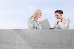 使用膝上型计算机的低角度观点的被集中的女实业家,当站立与大阳台的愉快的工友反对天空时 库存图片