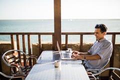 使用膝上型计算机的体贴的年轻亚裔人在咖啡馆有在海的看法 做自由职业者工作 库存图片